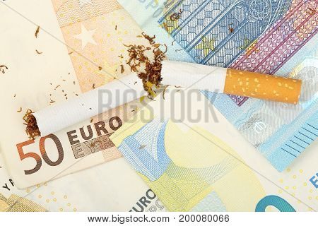broken cigarette on euro banknotes smoking is expensive