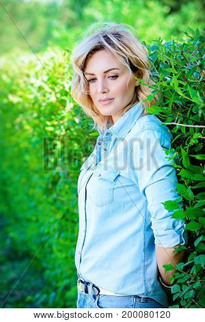 Beautiful middle aged woman is standing by the green hedge in the park on a summer day. Beauty, cosmetics.