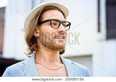 Happy hipster young man on a city street. Outdoor fashion.