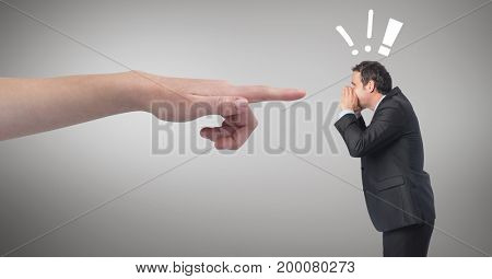 Digital composite of Hand pointing at angry business man against grey background with exclamation icons