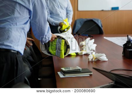 Man Takes A Protective Helmet From The Table