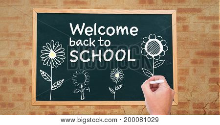 Digital composite of Hand drawing Welcome back to school text and flowers  on blackboard