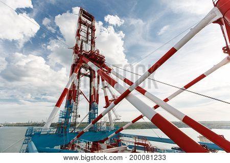 The Red-white Loading Crane Near The Sea