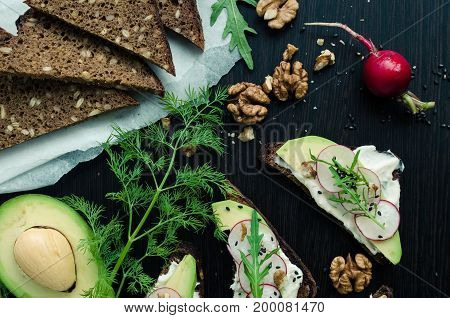 Sandwiches with avocado radish arugula cheese and nuts on a rye bread with sunflower seeds for healthy breakfast on dark wooden background. Vegetarian food. Top view.