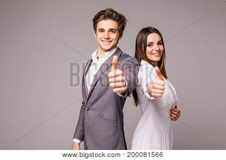 Two Smiling Happy Business People In Formalwear Showing Thumbs-up On Gray Background