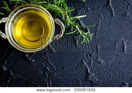Rosemary and olive oil on dark stone table. Herbs and spices concept. Cooking ingredients. Food flat lay. Creative layout with place for text. Copy space. Top view.