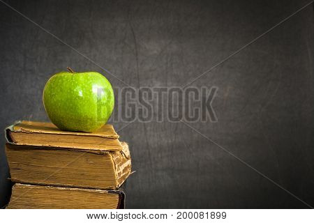 Green Apple On Old Book Against Blackboard