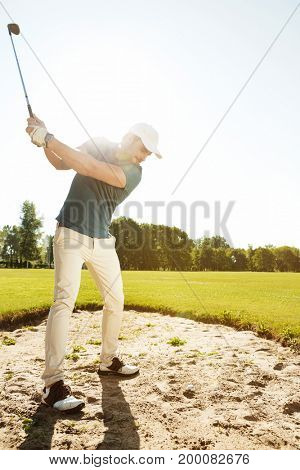 Male golfer about to hit ball out of a sand bunker while playing on a green course