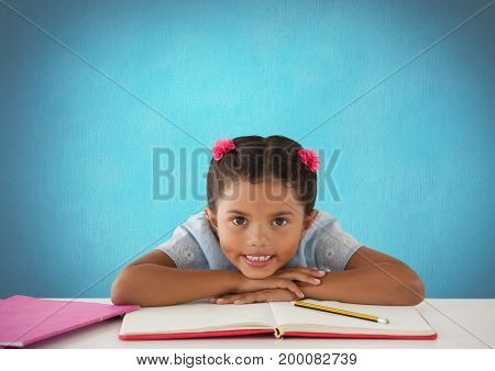 Digital composite of Schoolgirl at desk with blue background