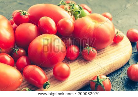 Various colorful tomatoes on wooden board on dark stone table. Different kinds of fresh organic tomato on black concrete background. Farm healthy eating concept. Selective focus.