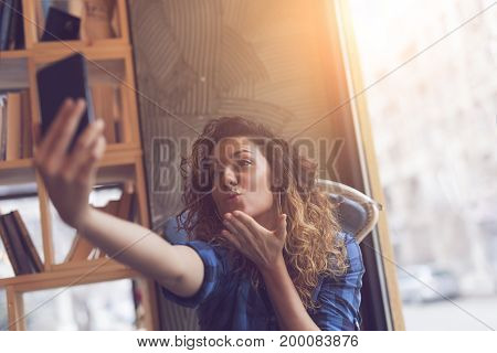 Beautiful young woman sitting in a coffee shop taking a selfie