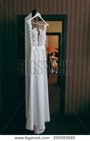 The beautiful wedding dress hanging in a room