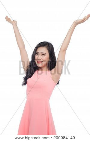 Happy young asian woman raise hands over white.
