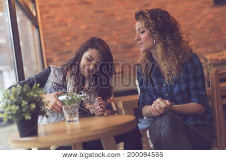 Two girls sitting in a coffee shop pouring a glass of detox water with mint leaves and having a conversation. Focus on the girl on the left