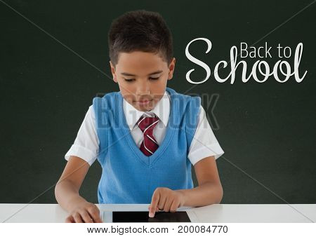 Digital composite of Happy student boy at table using a tablet against green blackboard with back to school text
