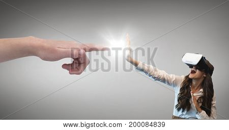 Digital composite of Hand pointing at surprised woman in VR headset against grey background