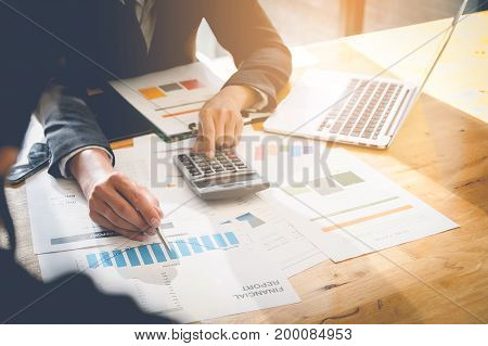 Consult financial concept. Business man pointing at papwework and using laptop computer.