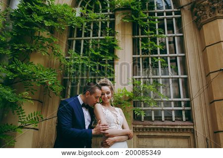 A Wedding Couple Is Standing On The Steps Of A Building