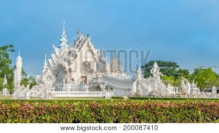 Wat Rong Khun The White Abstract Temple and pond with fish in Chiang Rai Thailand. Popular and famous in
