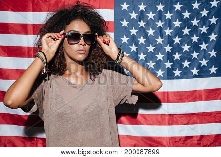 Picture of serious african young lady wearing sunglasses standing over USA flag. Looking aside.