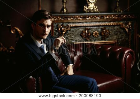 Handsome well-dressed young man in a room with classic interior. Business style. Luxury.