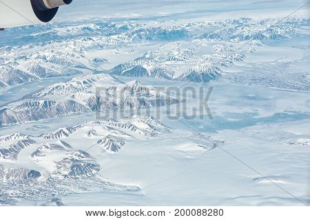 Aerial view of the Greenland with mountain, ocean and ice holes with part of airplain