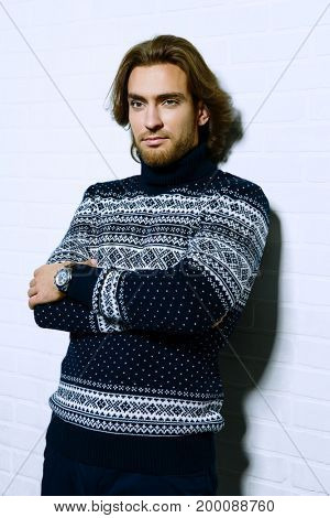 Handsome young man wearing sweater over white background. Winter fashion. Hairstyle. Studio shot.