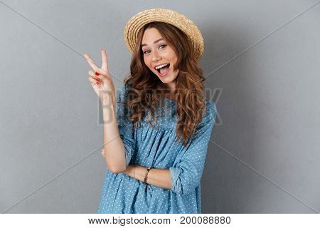 Photo of smiling young pretty woman standing over grey wall wearing hat showing peace gesture. Looking camera.