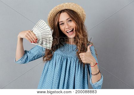 Picture of excited young happy woman standing over grey wall wearing hat holding money. Looking camera showing thumbs up.