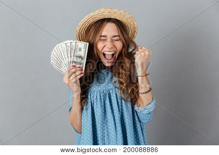 Image of excited young cheerful woman standing over grey wall wearing hat holding money. Eyes closed.