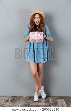 Image of surprised young pretty woman standing over grey wall wearing hat holding gift. Looking camera.