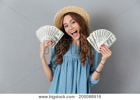 Picture of excited young happy woman standing over grey wall wearing hat holding money. Looking camera.