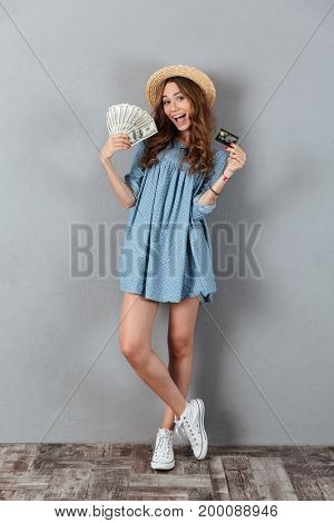 Photo of happy young pretty woman standing over grey wall wearing hat holding money and credit card.