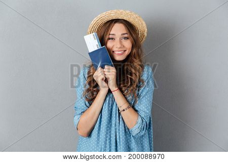 Image of happy young pretty woman standing over grey wall wearing hat holding passport and ticket. Looking camera.