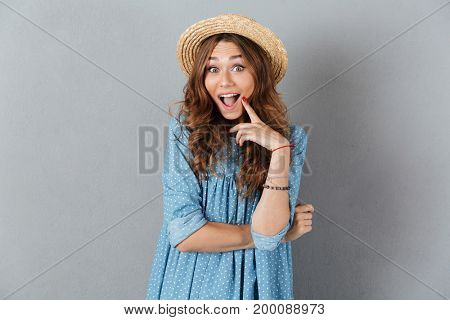 Picture of happy young pretty woman standing over grey wall wearing hat. Looking camera.