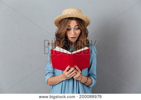Image of shocked young pretty woman standing over grey wall wearing hat reading a book. Looking aside.