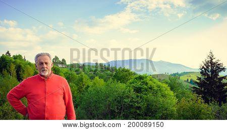 Senior man and beautiful mountain landscape. Looking at the camera. Serious senior man with gray hair and beard. Horizontal image.