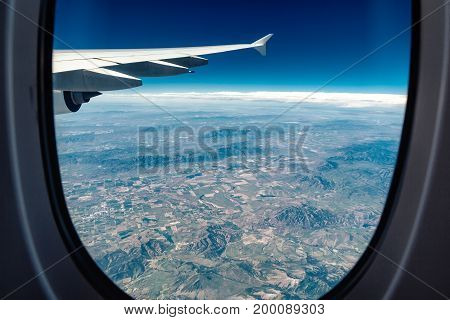 View from airplane window on circled fields with part of airplain