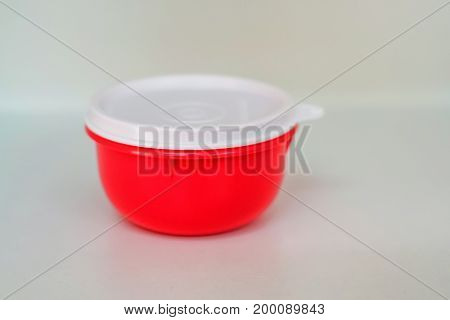 Close up modern red plastic food container with white lid isolated on white background