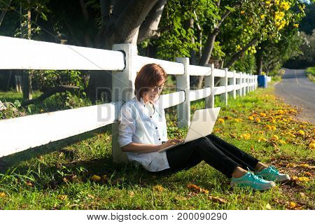 Young women lying in summer grass playing laptop and relax sunny day greenery 2017