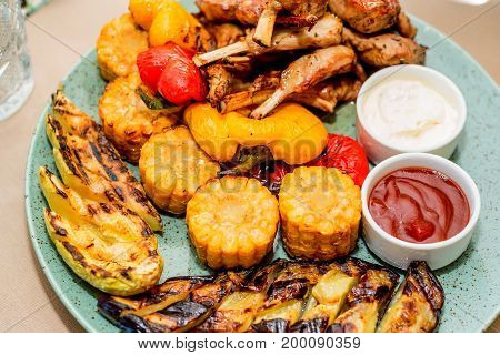 Close up plate with grilled meat ribs and vegetables with sauses