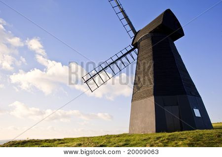 Old Wooden Smock Windmill Landscape Against Vivid Blue Sky With White Clouds