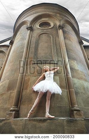 Low angle shot of a graceful ballerina posing elegantly on the wall of a big old castle outdoors.