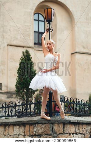 Beautiful young female ballet dancer performing near street lamp in the city center.