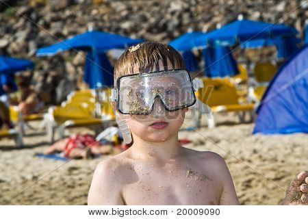 child boy with diving goggles is playing  at the sandy beach
