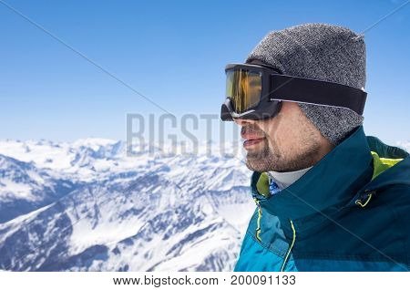 Portrait of man wearing ski glasses and cap while looking the snowy mountains. Closeup face of sporty guy contemplate the snowy. Satisfied skier smiling and wearing ski mask in mountains.