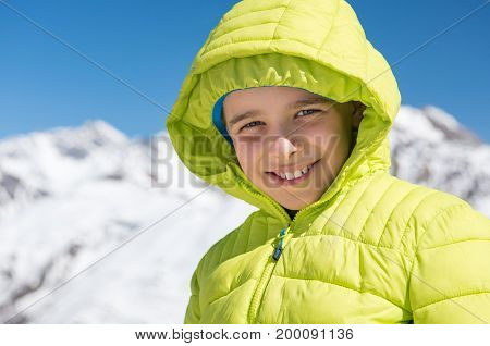 Portrait of happy little boy in winter clothes smiling and looking at camera. Close up face of joyful child enjoying winter vacation in snowy mountain. Kid in green jacket looking at camera.