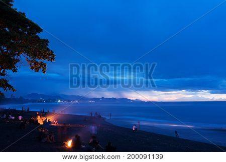 Pre-sunrise hour on black sand beach. Bali Island with view to Lombok Island. Indonesia.