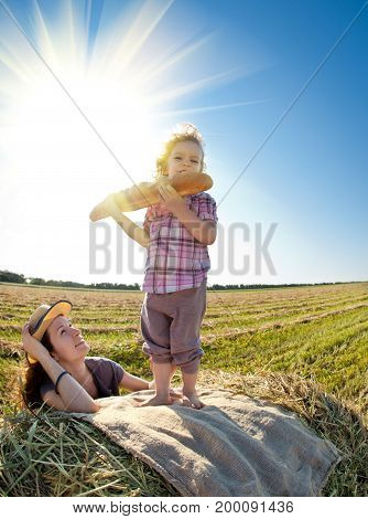 Happy woman and child eating bread in wheat field against blue sky background. Shot was taken with fisheye lens