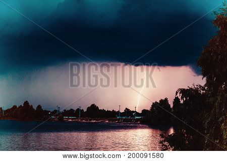 A tropical thunder storm over a country town with lightning strike on seaside